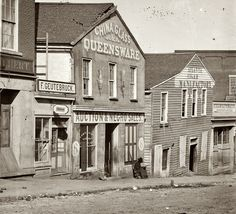 """""""Auction & Negro Sales. 1864."""" Whitehall Street, Atlanta, 1864. This photo of a black Union soldier posted at a slave auction house in Atlanta is one of hundreds taken by George N. Barnard during Gen. Sherman's occupation of the city in the fall of 1864. Many were destroyed in the conflagration that erupted upon Sherman's firing of Confederate munitions stores when he departed on Nov. 15."""