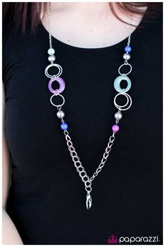 A collection of purple, Lucite, and Classic Blue beads and hoops combine with silver accents along a silver chain. A lobster clasp hangs from the bottom of the design to allow a name badge or other item to be attached. Features an adjustable clasp closure.  Sold as one individual lanyard. Includes one pair of matching earrings.
