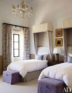 The Classic Cloth plaid used on the beds and the curtains' leafy Schumacher print add a spirited vibe to a bedroom in Gisele and Tom Brady's Los Angeles home; the striped pillows and Joan Behnke–designed storage ottomans are both covered in Loro Piana fabrics, and the chandelier is by Axel Vervoordt.