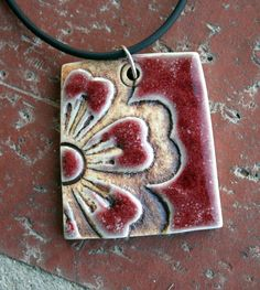 Bold, graphic rustic flower surrounded by a copper red glaze with greyish outline. Love this combination! Measures approximately 2 long by 1.5 wide.