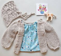 """A cosy little flatlay with our new vintage crochet bonnet in """"Stone"""". Link in bio   #malindajanehandmade #handmade #madewithlove #australianmade #cotton #crochetbonnet #crochet #babybonnet #lacebonnet #babyfashion #auskidfashion #shopsmall #babyclothes #crochetcotton #handmadeaccessories #bonnet #etsybaby #etsy #girlaccessories #vintagebaby #vintagecloset #littlegirl #flatlay  #cardigan #babycardigan #crochetcardigan by malindajane_handmade"""