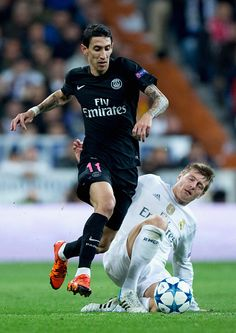 Angel Di Maria of PSG is tackled by Toni Kroos of Real Madrid during the UEFA Champions League Group A match between Real Madrid CF and Paris...