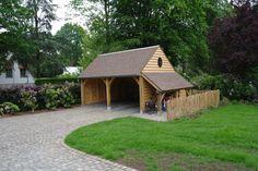 Eiken bijgebouw als dubbele carport met aan de zijkant een houtberging en een smeedijzeren ossenoog.