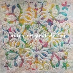 White applique on a rainbow sherbet colored batik background.