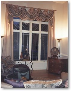 Double Swagged Pole Swags With Soft Fold Panels Accent This Leaded Glass  Window.