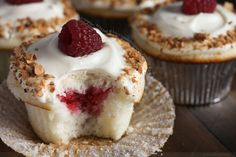 almond flavored cupcakes whipped white chocolate ganache frosting and raspberry jam filling