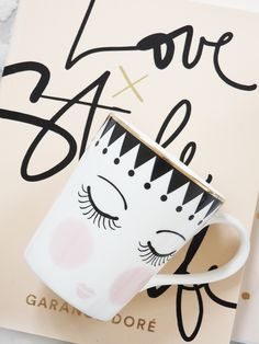 """Our fabulous """"Closed Eyes"""" Polka Dot Coffee Mug by Miss Etoile features printed gold tassels, polka dots and rosy pink cheeks with lips."""