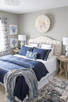 See my new guest bedroom updates including this gorgeous white juju hat wall decor that I hung above the bed, new navy blue duvet cover with matching shams and new column table lamps! Decorating this room has been so much fun! #bedroom #decor #diydecor