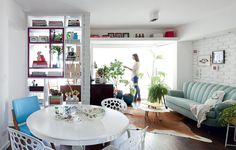 O apartamento tem apenas 70 m², mas a sala é ampla, com poucos e pequenos móveis. A prateleira no alto oferece mais espaço para guardar livros e expor quadros da arquiteta Marcela Madureira. Como tudo é branco, o elemento passa quase despercebido