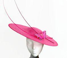Pamela rosa fucsia decorada con raquis y mariposa rosa. Es un tocado fucsia…
