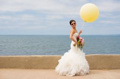 We love our fun bride running by the beach and carrying a large yellow balloon! | Always Flawless Productions | A San Diego Wedding Planning & Design Studio