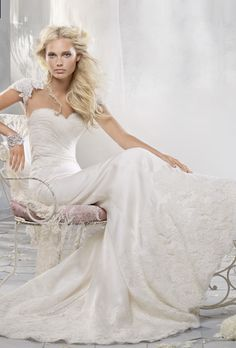 Brides: Alvina Valenta. Ivory silk satin organza soft fluted bridal gown. Strapless sweetheart neckline with Ivory alencon lace on bodice and Ivory silk chiffon draping overlay. Deep border of alencon lace surrounds hemline, sweep train. Shown with an Ivory alencon lace bolero jacket.
