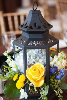 flowers in a lantern as a centerpiece. i love the way they are overflowing!