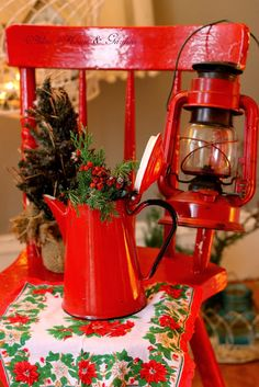 Red chair, lantern, enamelware coffeepot with greens, vintage Christmas handkerchief. (Aiken House & Gardens: A Pop of Christmas Red)