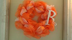 Orange deco mesh wreath (represents kidney cancer) with white deco added. Includes orange & white polka dot ribbon, wht butterfly and letter R handpainted wht then accented with clear rhinestones.