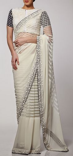 A resplendent white net saree with tone-on-tone stonework borders. The saree comes with a matching white blouse with houndstooth sleeves. The blouse is embellished with tone-on-tone stonework. Designer: Neeta Lulla