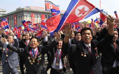 North Korea marked the 65th anniversary of its founding on Monday with a military parade in Pyongyang. North Korean scientists wave their national flag during the military parade. (Picture: AP Photo/Jon Chol Jin)