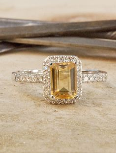 A golden yellow citrine is framed by a halo of brilliant diamonds, extending halfway around the band. This vintage inspired engagement ring is one-of-a-kind.