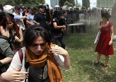 Turkish riot police use tear gas during a protest in central Istanbul. A Turkish riot police officer uses teargas against demonstrators protesting against the destruction of trees in a park in Taksim Square. Women Rights, Powerful Images, Iconic Photos, Famous Photos, Lady In Red, Pictures, Destruction, Riot Police, Madame Red