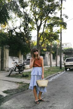 Nisi is wearing: Straw bag, striped skirt with volants, Céline Baby Audrey sunglasses, Nina Kastens Stella Earrings, Hermès Oran sandals - teetharejade.com