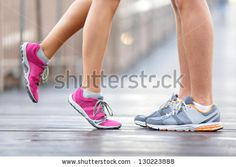 Love sport concept - running couple kissing. Closeup of running shoes and girl standing on toes to kiss boyfriend during jogging workout training outdoors on brooklyn bridge, New York City. - stock photo