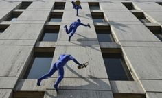 Walls and Trumpets by Ofra Zimbalista  Sculptures of blue-clad men carrying musical instruments hang from the Maya House building in Borough High Street, South London, United Kingdom