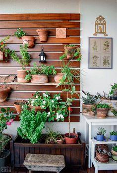 Jardim vertical na varanda deixa a sua casa muito mais leve e com frescor. Para montar o jardim vertical, você utilizar tábuas de ipê, que são parafusadas em uma das laterais do terraço. A aplicação de uma demão de stain ao ano protege a madeira. Os vasos podem ficar suspensos com arame.