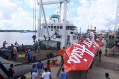 Workers load the tail of AirAsia flight onto a truck at Kumai sea port, in Central Kalimantan. - Provided by AFP Surabaya, Airbus A320, Location History, Aircraft, Asia, Fair Grounds, Boat, Critique, Travel