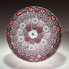 "Parabelle Glass millefiori paperweight. Composed in the classic period style, with concentric millefiori presenting a central white rose, encircled by complex canes in pink, lavender, red and white on upset muslin; signed/dated 1997. Limited edition of 10.Diameter 3 3/16"" http://www.lhselmanltd.com/"