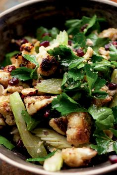 "NYT Cooking: In this memorable salad from ""Jerusalem,"" the beloved Middle Eastern cookbook from Yotam Ottolenghi, roasted cauliflower, celery and hazelnuts are combined with pomegranate seeds, fresh parsley, cinnamon and allspice. A sweet-tart vinaigrette finishes it off."