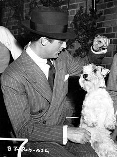Cary Grant plays with a dog on the set of Suspicion, 1941.