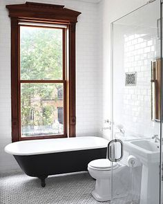 floor to ceiling subway tile, black claw-foot tub, ann sacks marble floor tile, and frameless glass shower.  love the architecture of the window.