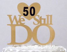 """Through all the years together We Still Do! Top your cake with our """"We Still Do"""" cake topper. • Ships in 1-3 business days • Made from 2 double sided 110-lb metallic or 104-lb glitter card stock (flake free) • Available in gold or silver • Attached with 2, 4-inch bamboo skewers • Reusable black vinyl numbers allow your cake topper to be used multiple times with any number  combination • Choice of san-serif or serif numbers • Remove skewers and have a treasured keepsake to remember your…"""