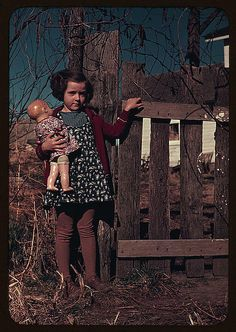 Girl with doll by fence, c. 1939 (LOC)