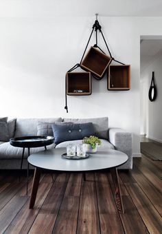 Scandinavian look in the living room with dark wooden floors and a creative idea with wooden bookcases hanged by rope.