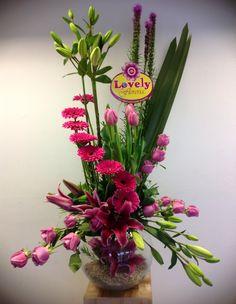 Arreglo floral con flores varias en pecera de cristal.