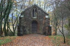 Rustic mausoleum in the woods for the MacGregor clan in Balquhidder, Scotland.  It is behind a stone wall with a locked gate on the way to the grave site of Rob Roy MacGregor.