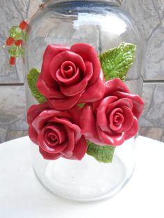 Pote de vidro com aplicação de rosas em biscuit na tampa e vidro. <br>O modelo do vidro é de palmito com a boca estreita medindo 7,5 cm. A tampa é de plástico modelo de rosca. <br>A altura do vidro com a tampa decorada é de 30cm.
