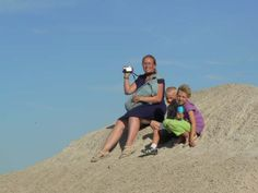 Sheri and kids climb a sand dune to video her husband and son riding ATVs