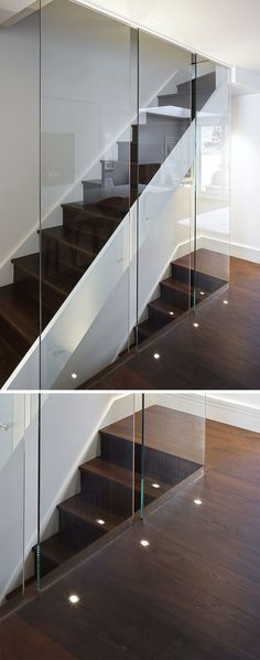 7 Interiors That Use Dramatic Uplighting To Brighten A Space // Small lights built into the floor of this home brighten the dark wood floor and contribute to the modern feel of the staircase.