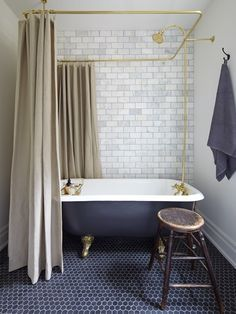 Hexagonal Bluestone marble floor tiles with classic honed Statuario Perla marble subway tiles for walls. Matte black paint makes a modern claw foot tub look vintage, and a linen shower curtain and dramatic brass rod give the tub presence..