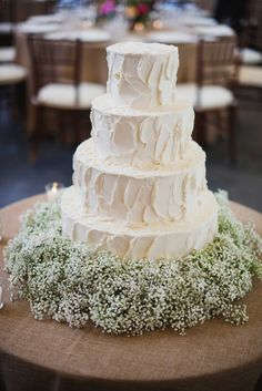 Simple white four layer wedding cake with baby's breath flowers at base