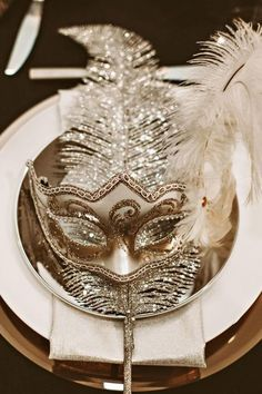 Looking to create a real party atmosphere for your wedding? This fun and glitsy place setting might do the trick! See more fab winter wedding table settings on Mrs2be.ie! #silver #masquerade #mask #feather