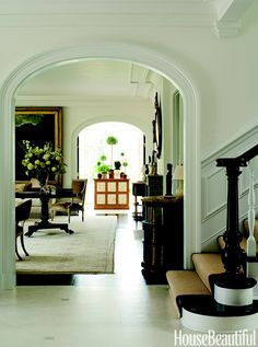 """Designer William Hodgins said, """"I felt like this wide walkway needed strong symmetry and strong furniture."""" To that end, he placed a pair of large Sheraton consoles against one wall in a Virginia house.  Foyer floors are faux-painted marble tile.   - HouseBeautiful.com"""