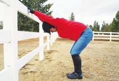 Arena-Rail Overhead Stretch: Stand half a body's length from the fence with your feet shoulder-width apart, bend at the waist, and place your hands on the top rail. Your arms, shoulders, and back should be flat. Relax your neck, breathe deep, and let your body settle into the stretch.    Payoff: Creates flexibility in your shoulders and promotes good posture before mounting up; stretches tight hamstrings in the back of your legs; stretches your calf muscles to allow for deep heels when you…