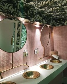 Tropical wallpaper on a bathroom ceiling makes a change, especially with pink tiles.