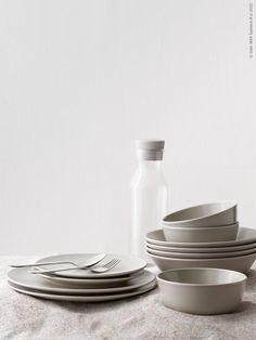 Serien DINERA med sin enkla form, dämpade färg och matta glasyr ger en rustik känsla och lyfter fram maten på bordet. DINERA servis i 18 delar, DINERA skål, DRAGON bestick, IKEA 365+ karaff med kork.