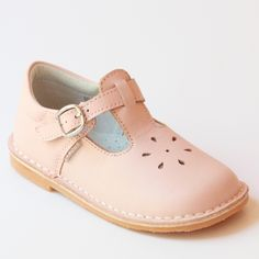 A L'Amour classic that is loved by many, these sweet pink leather mary janes come with an elegant perforated design. Sizes 5-13 (Toddler), 1-2 (Youth) We highly recommend checking the size chart for t
