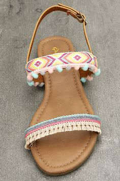 Greet the sunshine in the Danica Nude Embroidered Pompom Flat Sandals! These cute tan vegan leather sandals have blue, neon pink, beige, and gold embroidery, plus pompom accents and fringe. Adjustable gold buckle ankle strap.