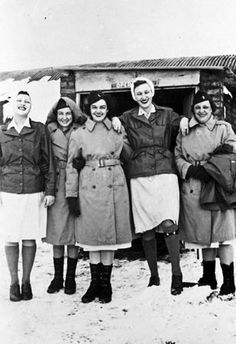 Estelle Garner Ptaszynski (center) and four other Army Nurse Corps members stand outside the field hospital in England on a snowy day, 1943-1945. Garner is wearing the Army Nurse Corps overcoat ~